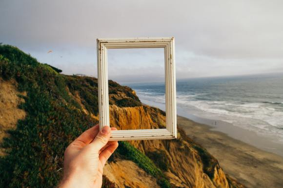 Uma mão segura a moldura de um porta-retratos em uma bonita paisagem