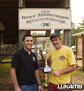 Track Manager Rich Schmidt presents Zimmermann Cup winner Barry Carsten with the commemorative trophy.