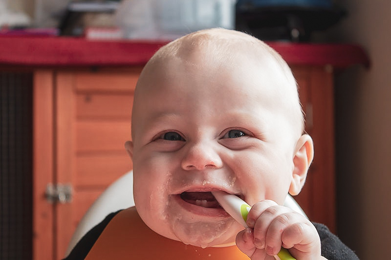 cheeky baby chewing on a weaning spoon and grinning