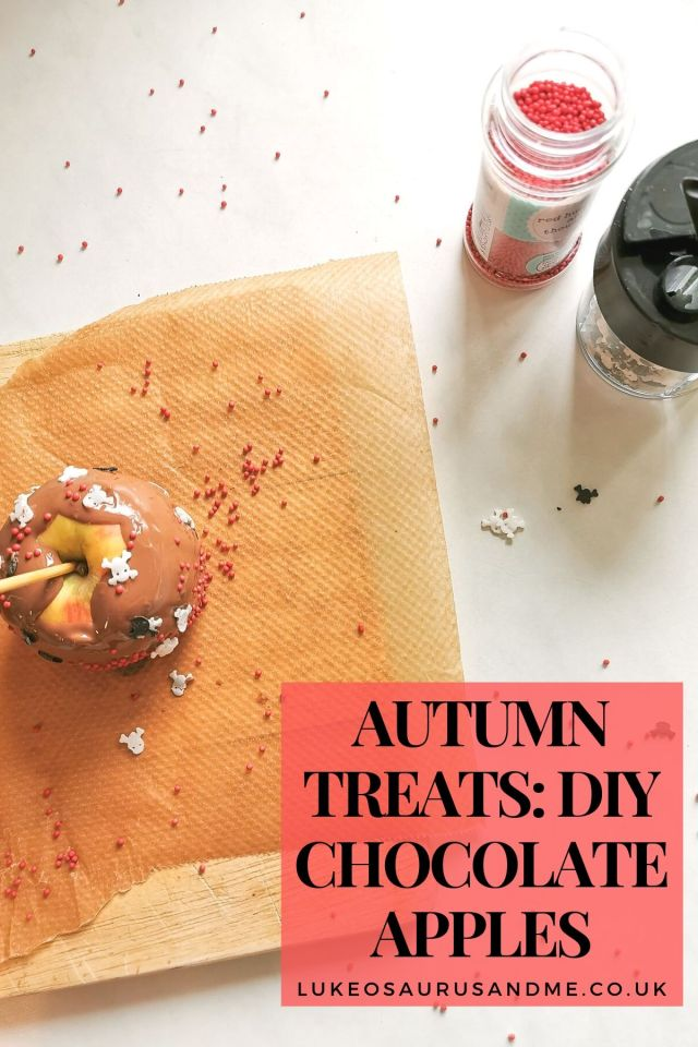 A chocolate covered apple covered in sprinkles sitting on some grease proof paper. 2 pots of sprinkles are in the top right hand corner.  The text says 'Autumn Treats: DIY Chocolate Apples'