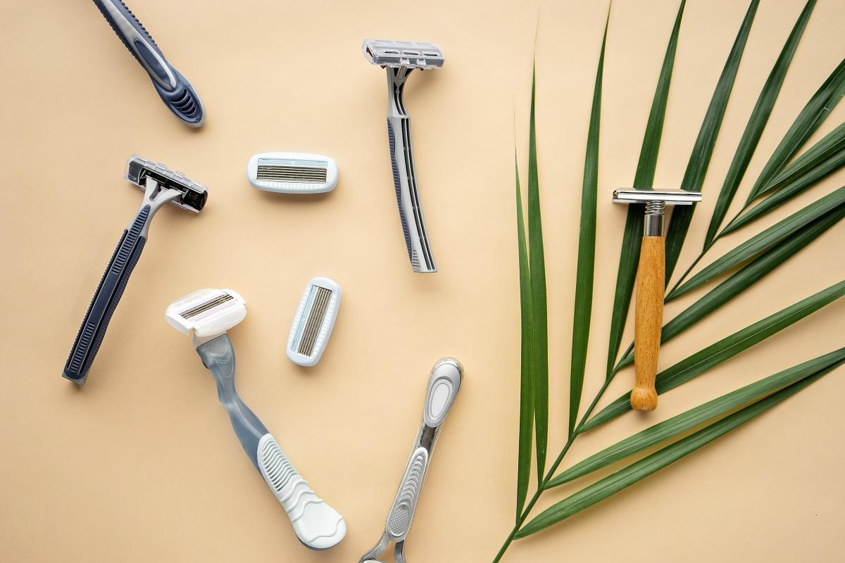a flat lay consisting of disposable razors and one eco friendly razor resting on a fern leaf.