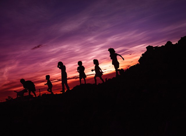 Children and their dog running down a hill silhouetted against the sunset.