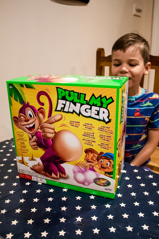 The Bull My Finger board game box on a table with a child sat behind it.
