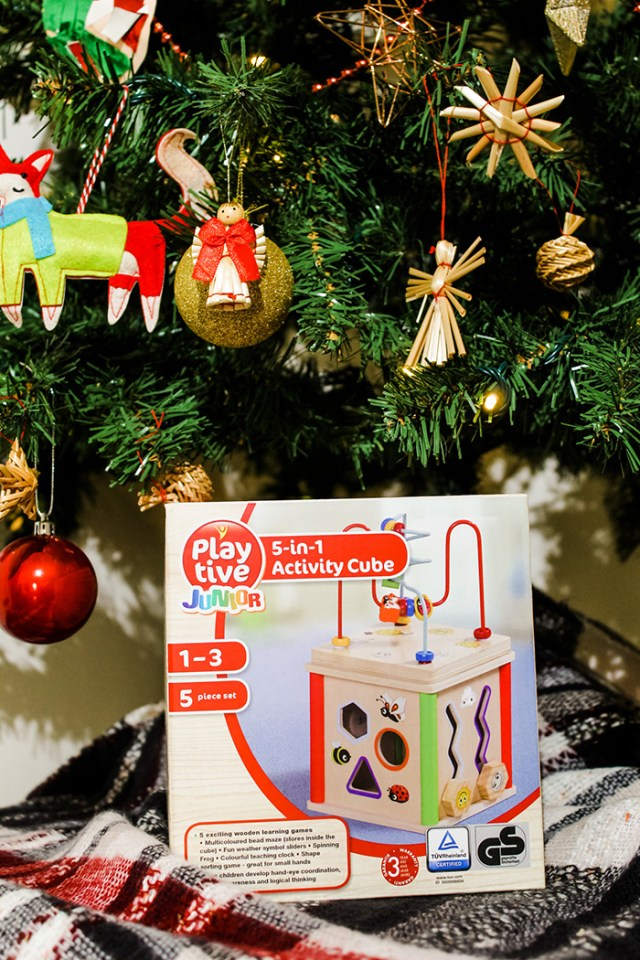 Playtive Junior 5 in 1 activity cube in front of a Christmas tree.