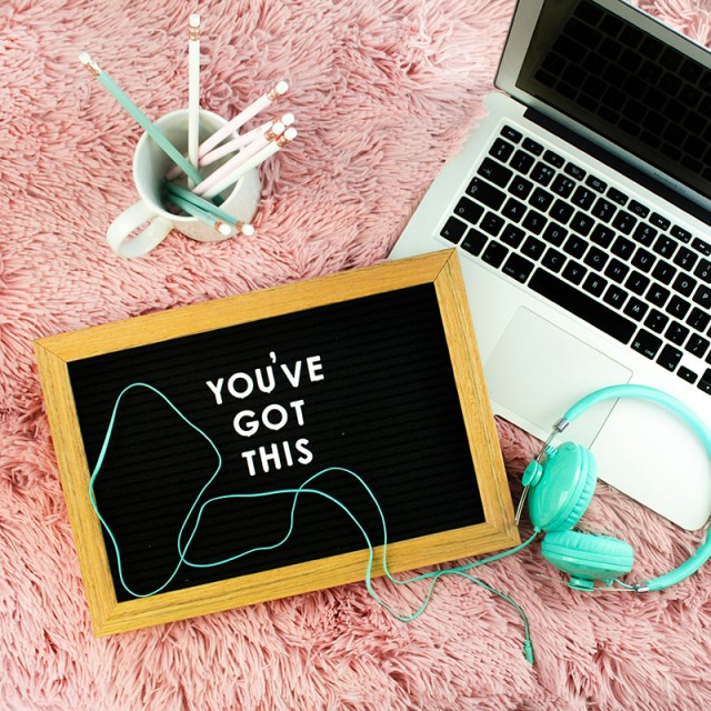 Flat lay of laptop, pens,, headphones and a board that says you've got this.