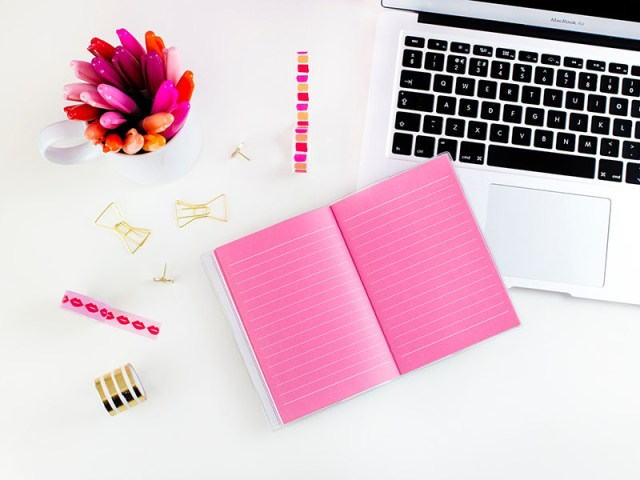 Flat lay of an open pink notepad, some washi tape, bright pink pens and a laptop on a white background for a blog post on 2020 goals on Lukeosaurus and Me.