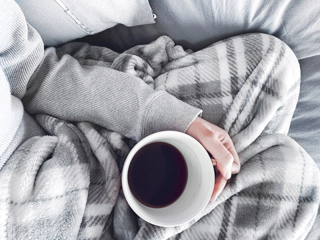 woman holding black coffee under a grey blanket on a grey sofa for a blog post about moving house