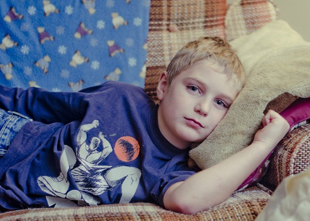 boy lying on sofa, head resting on a cushion for a blog post on childhood illnesses