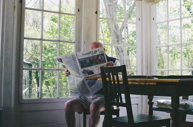 Elderly man in his house sat at a table reading a news paper for a blog post about age uk mobility