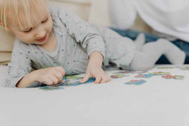 girl in gray polka dot long sleeve shirt playing puzzle on white textile