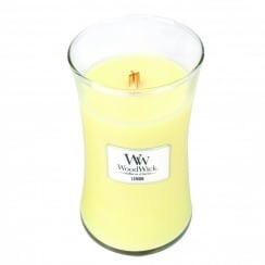 A large yellow wax candle in a glass jar.