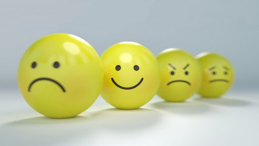 happy and sad emoticon faces on yellows balls