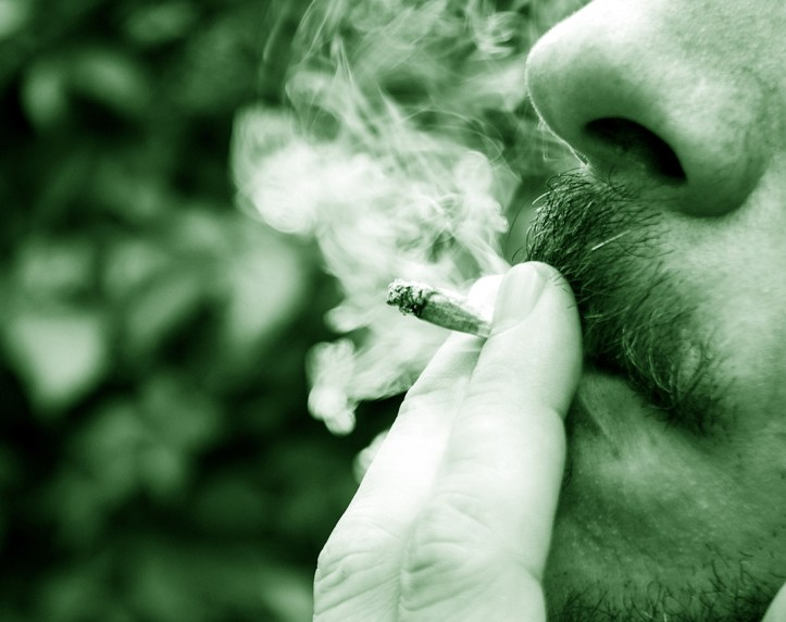 Close up of a male smoking cannabis cigarette.
