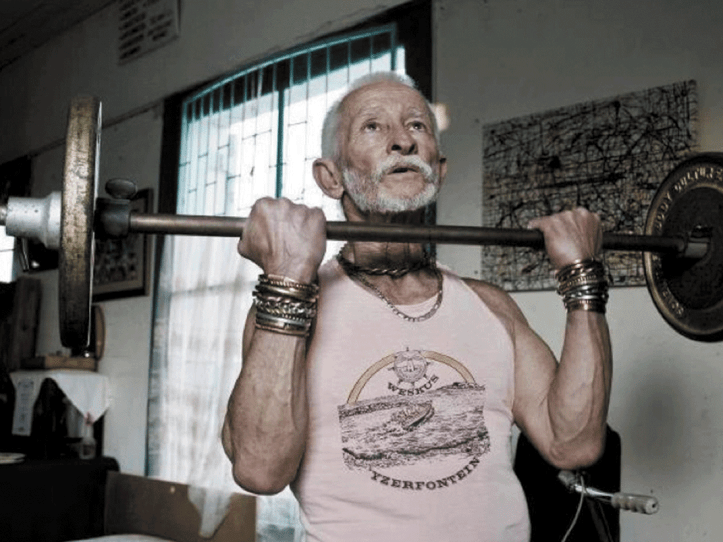 Aged man lifting a heavy weight for exercise
