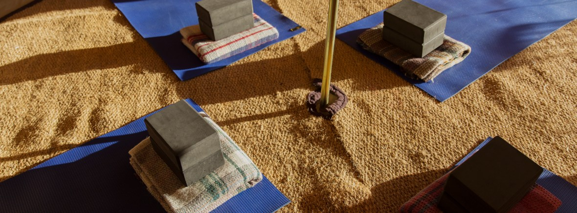yoga mats, blocks and blankets inside a bell tent
