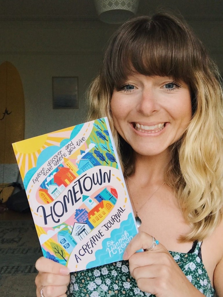 Creator, Hannah Bevan holding a copy of Hometown, a creative journal