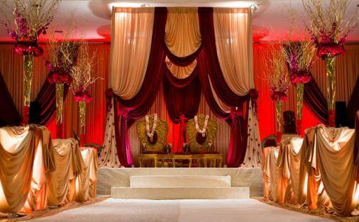 украшение свадебного зала высокими вазами с красными цветами