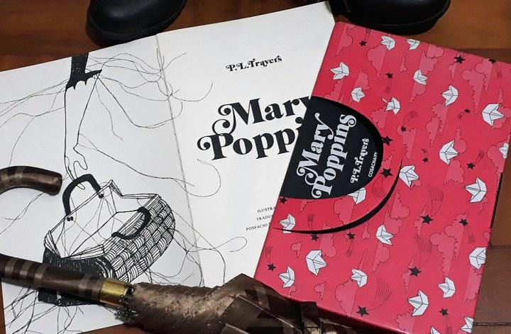 Mary Poppins: Foto do livro Mary Poppins, publicado pela editora Cosac Naify, aberto na folha de rosto, onde se lê o título e o nome da autora e uma ilustração de bolsa na página ao lado. O livro está parcialmente dentro de sua luva, que simula a maleta da personagem. Na parte de cima da imagem se vê a ponta de duas botas marrons e em baixo um guarda-chuvas da mesma cor.