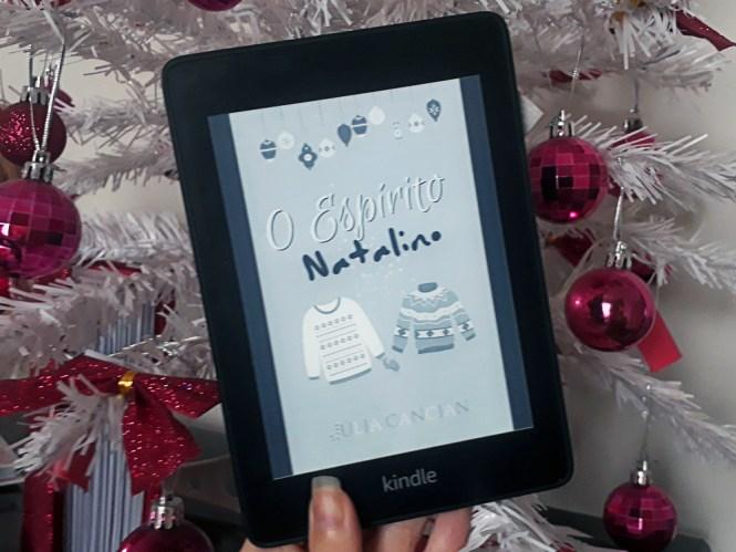 O Espírito Natalino: foto do aparelho Kindle com a tela ligada em que a capa do livro aparece em destaque. Ao fundo, galhos de uma árvore de natal branca com enfeites rosa choque variados.