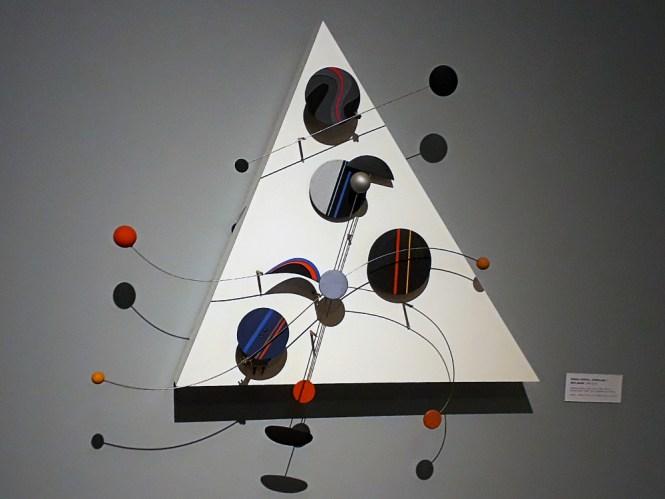 Objeto cinético de fundo triangular, com formas circulares planas e maciças coloridas fixadas em cabos retos e ondulares, permitindo movimento determinado pelo artista, não perceptível na imagem, que é estática.