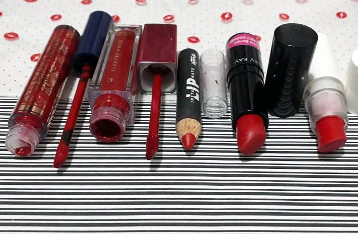 Foto de cinco batons vermelhos, entre líquidos, lápis e em bala, deitados abertos lado a lado, alinhados. Eles estão sobre papéis de duas estampas diferentes, um com símbolos de bocas vermelhas e o outro listrado de preto e branco.