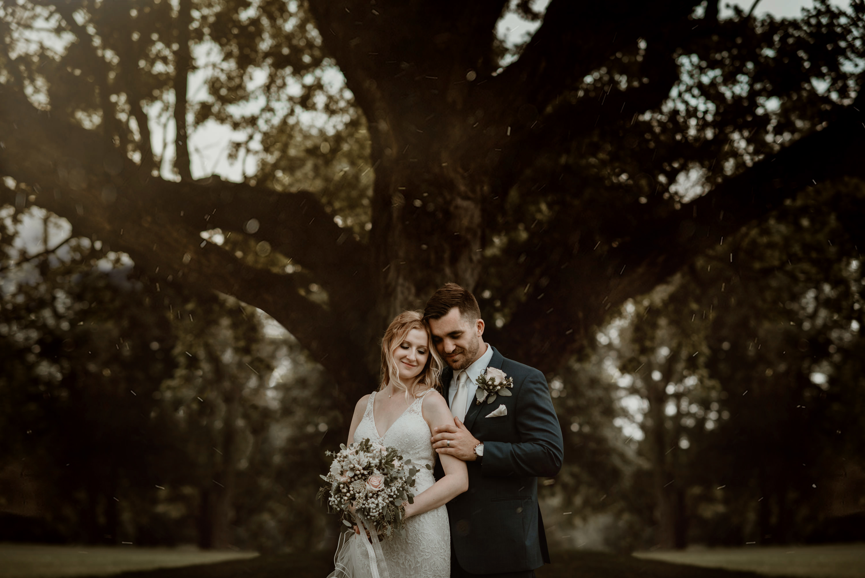 Bride and groom smiling and standing close under a huge oak tree.