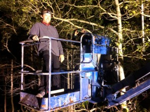 Joe Martin piloting a boom lift to install LEDs high above the forest floor.