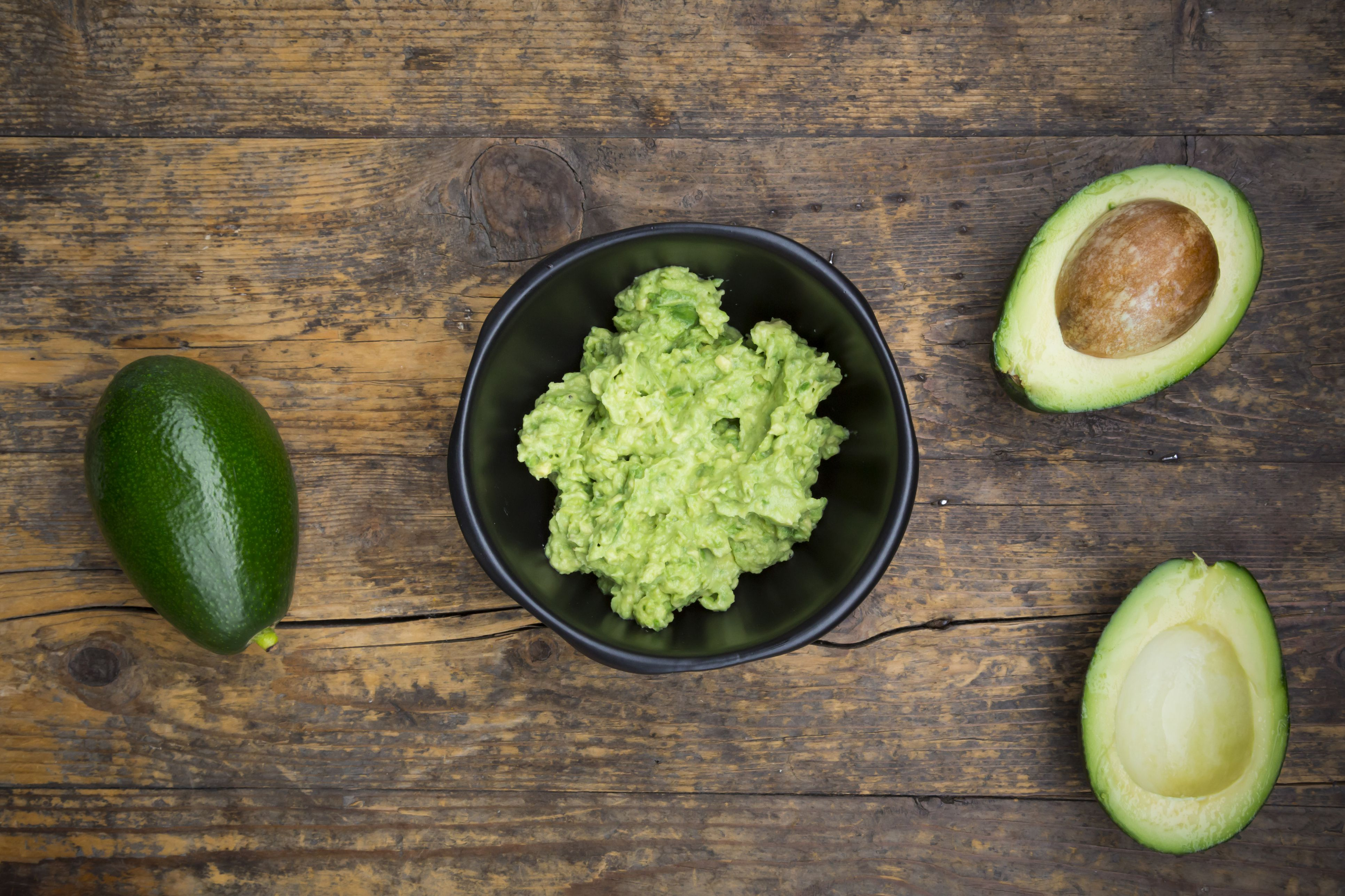 bowl-of-guacamole-and-whole-and-sliced-avocados-on-dark-wood-597065267-5997166daf5d3a00110910d9