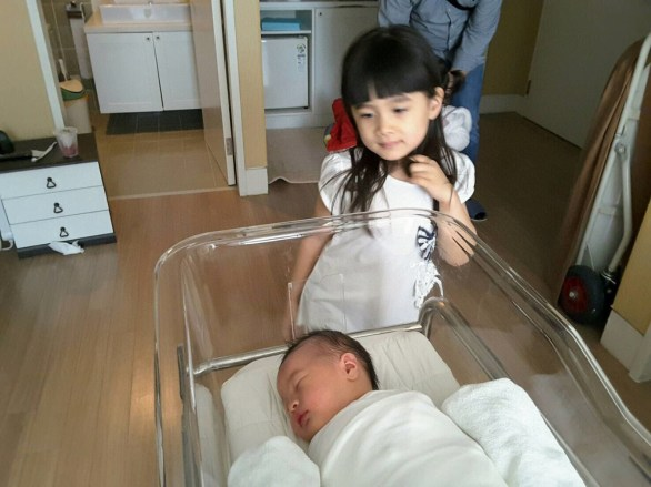 Big sister Eva meets the baby for the first time. A little wary...