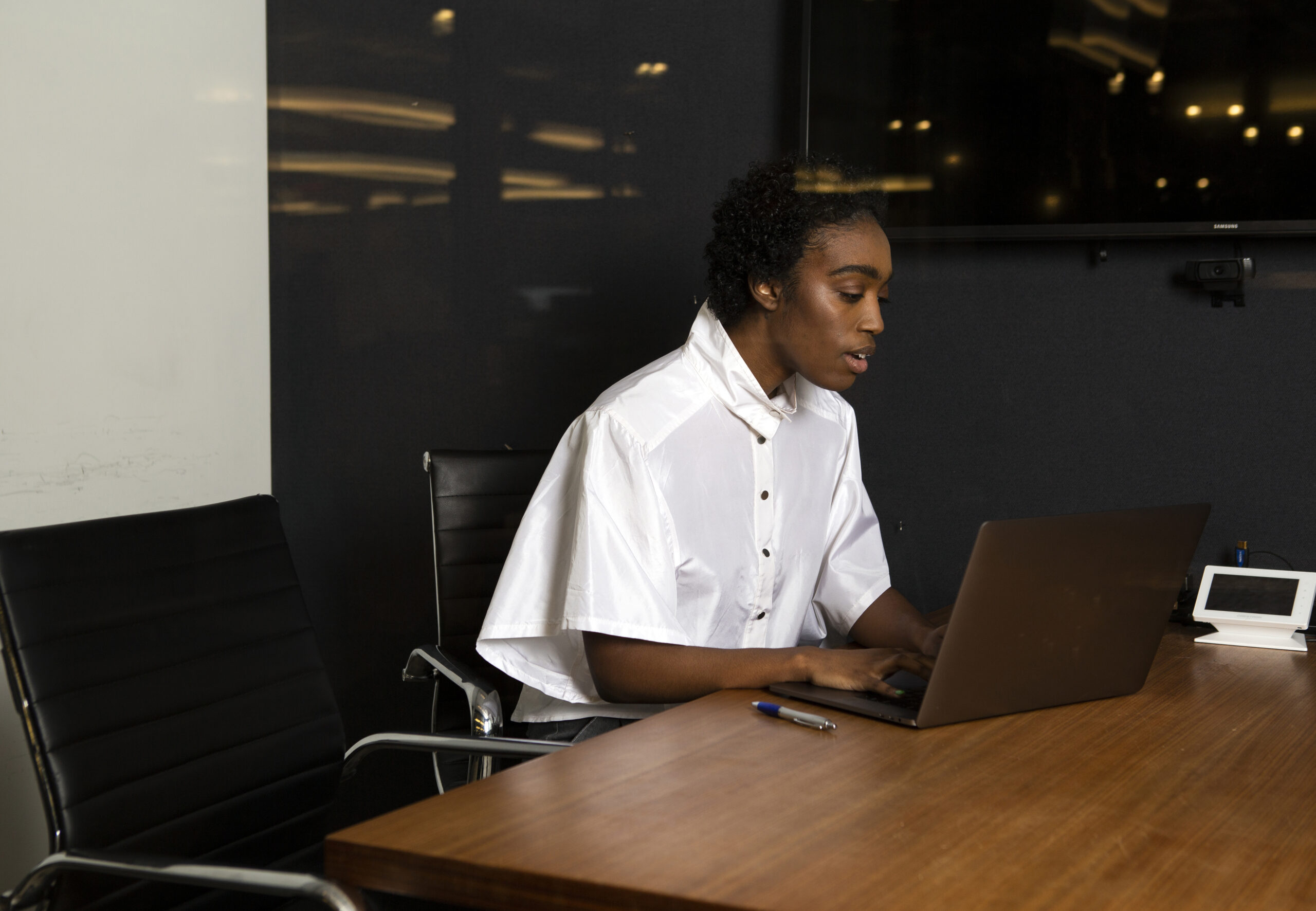 A non-binary person using a laptop at work.