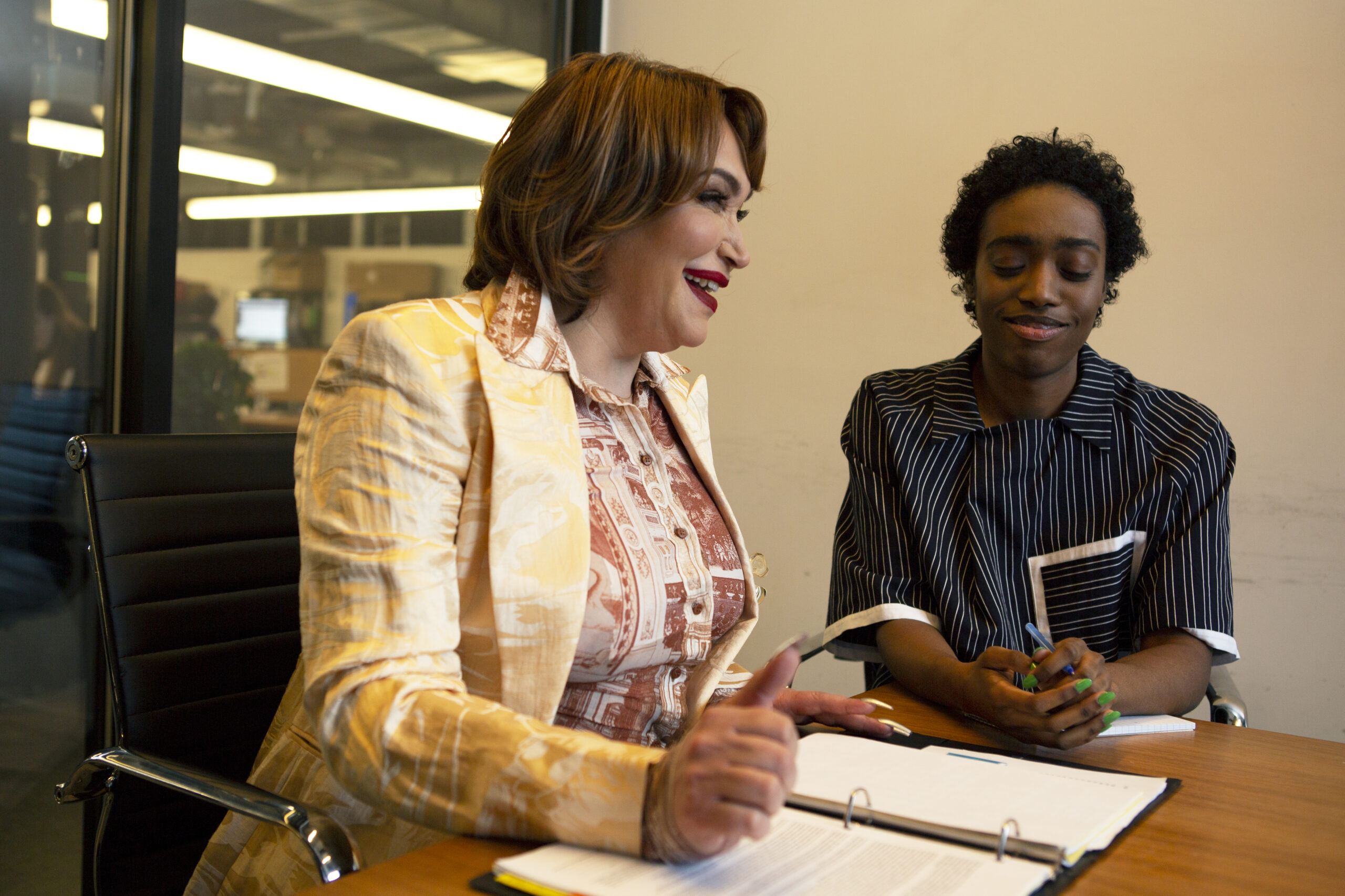 Two colleagues a transgender woman and a non-binary person laughing in a meeting at work