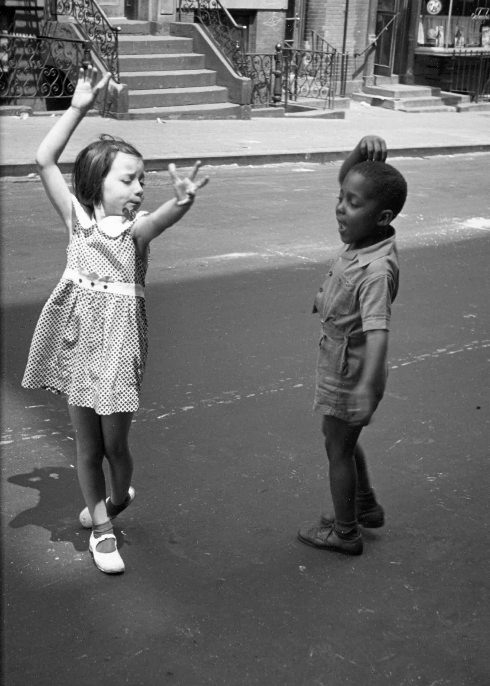 Un nen i una nena ballant al carrer.