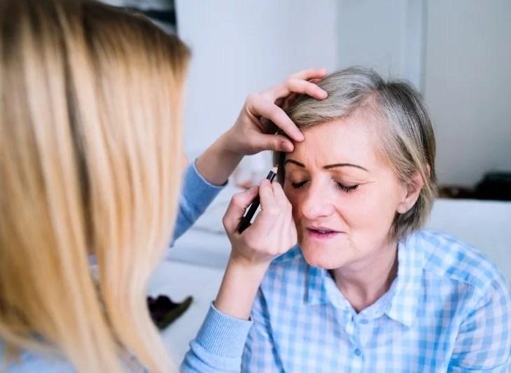 cancerdrabbad kvinna sminkar sig