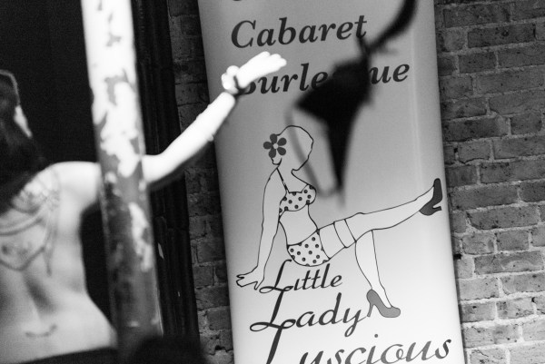 Woman with back towards camera posing in front of Luscious Cabaret Logo