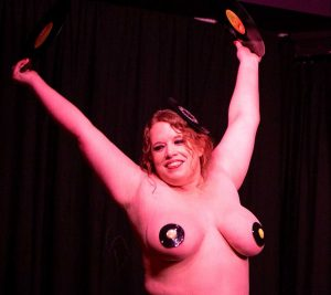Woman Posing at the end of her burlesque routine showing off her body with record burlesque pasties to cover her nipples