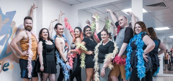 A group of eight people wearing feather boas posing with their right arms in the air and hands on their hips