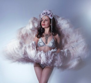 Bootsy Bonafonte holding feather fans in a showgirl style