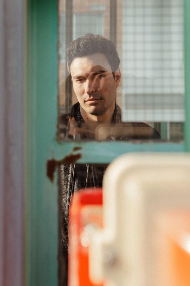 Peter Serrado reflection in window