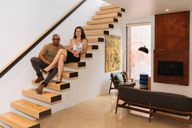 Ana Silva and Carl Cassel sitting on the stairs of their home