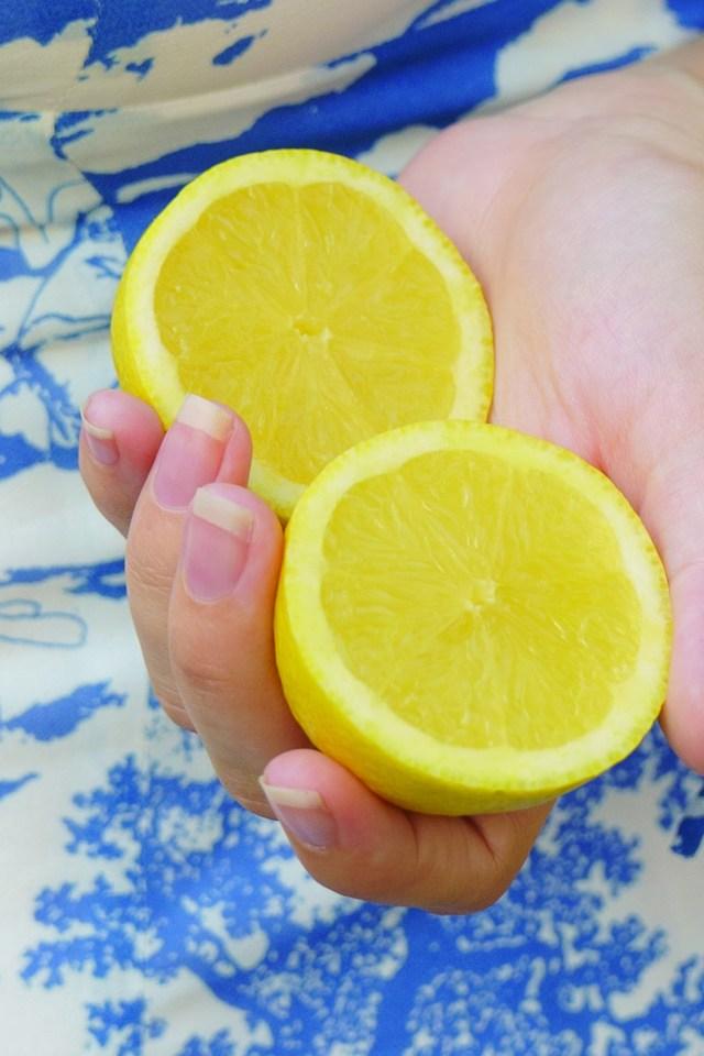 Two lemon halves in hand