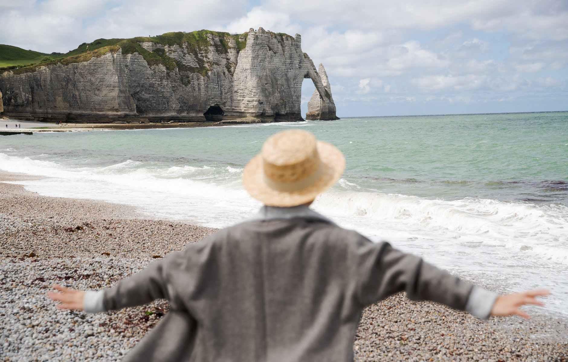 unrecognizable traveler in hat on shore near wavy sea