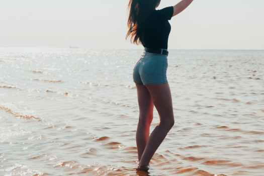 woman in black shirt and blue denim shorts standing on beach