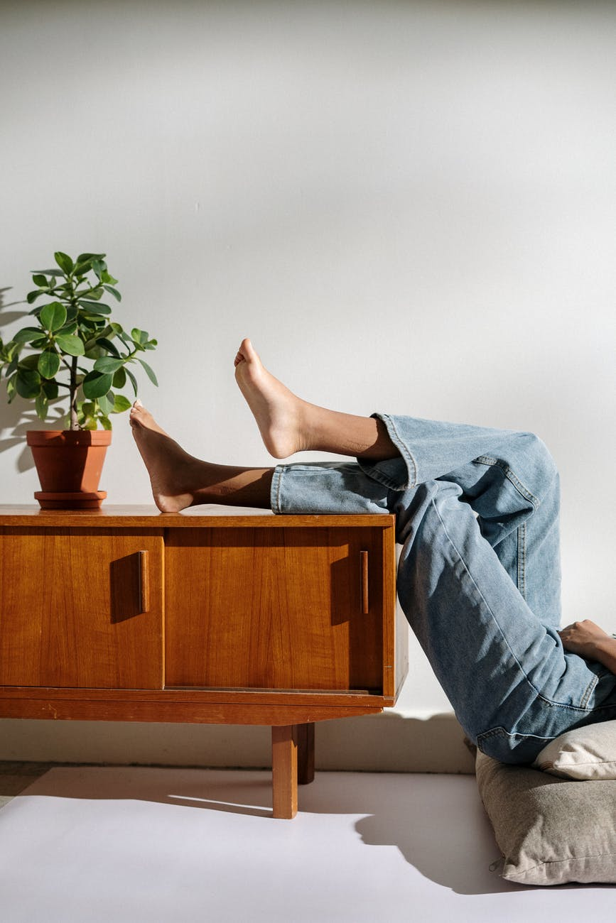 person in blue denim jeans lying on brown wooden table