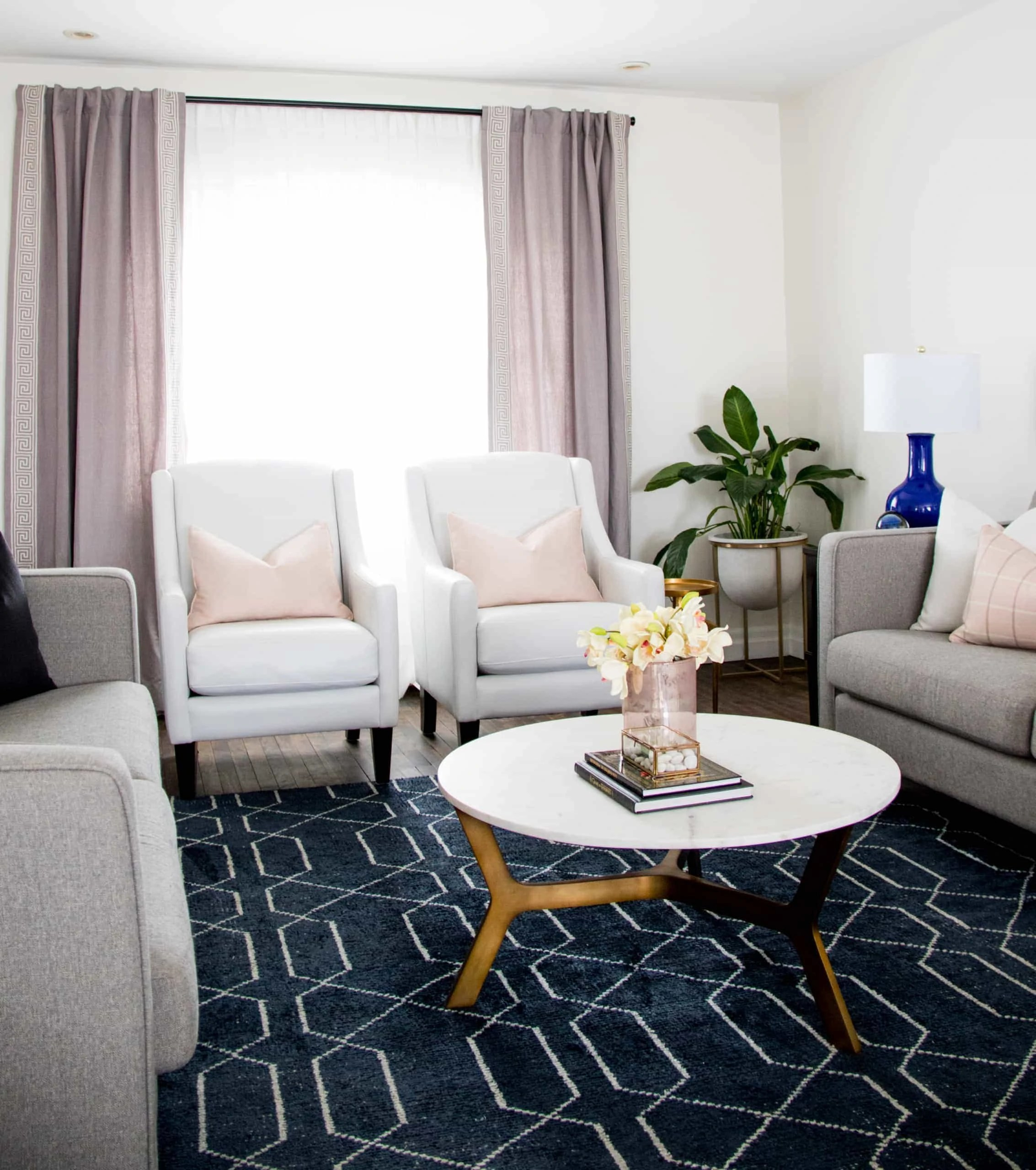 Bright living room with a focus on two white chars against a window
