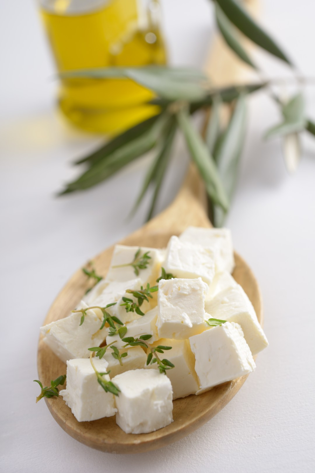 shutterstock_126397562-Diced feta cheese in a wooden spoon against olive oil