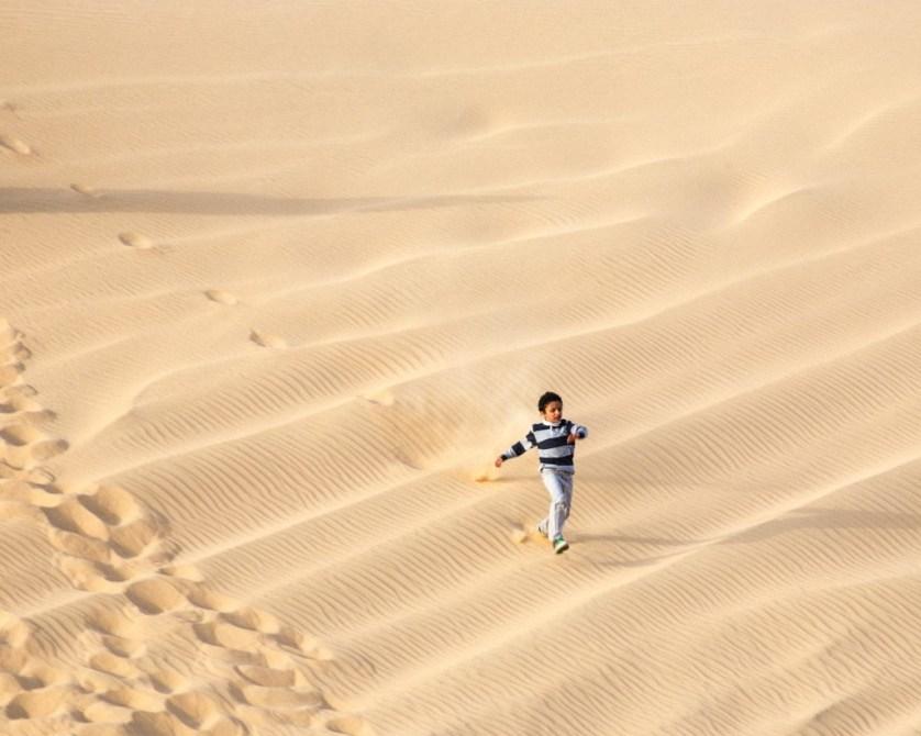 Child runs down the dunes.