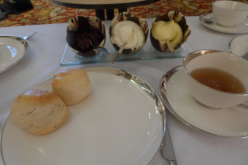 Scones with Devonshire cream, lemon curd, and jam in chocolate shells.