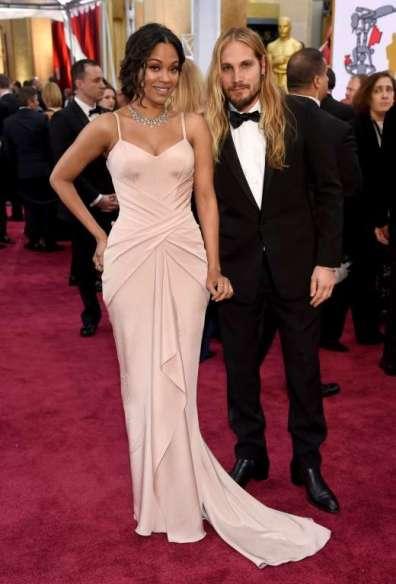 Zoe Saldana (trái) khoe đường cong trong một thiết kế thảm đỏ của Atelier Versace. Mái tóc của Marco Perego, chồng cô, làm chúng ta nhớ đến Jared Leto