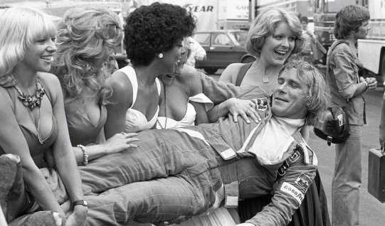 James Hunt, som han huskes bedst – iført køredragt og omgivet af smukke kvinder. Den britiske racerkører og playboy levede et liv, de fleste end ikke turde drømme om og vandt desuden et verdensmesterskab i Formel 1.