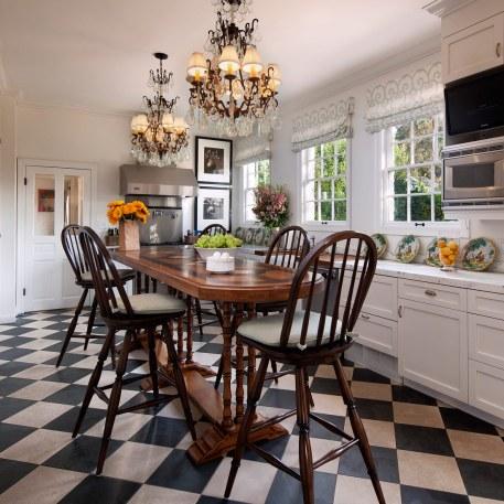Det forhøjede massive spisebord med dertilhørende træstole er køkkenets midtpunkt. Den landlige cottagestil bliver understreget af det sort-hvid-ternede gulv.